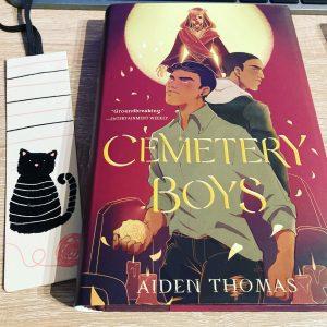 """Das Buch """"Cemetery Boys"""" von Aiden Thomas liegt neben einem Lesezeichen, auf dem eine schwarze Karze abgebildet ist, auf einer Holzoberfläche"""